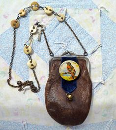 """""""The Divine Miss O Coin Purse Necklace"""" (""""a celluloid button issued by the Audubon Society, in the '30s, mounted on a vintage blue velvet ribbon over a soft leather coin purse from Milan Banking Co., Tennessee, on a recycled chain linked with bone underwear buttons, tagged with a sweet, small, rusty key from Eagle Lock Company, of Terryville, Connecticut..."""")"""