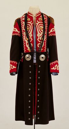 Osage woman's wedding coat -  late 19th century. Dark blue wool, shoulders and cuffs have wide red satin ribbon; two rows of four each gold 1850s staff buttons with eagle design on front yoke; gold epaulets;  row of ten silver buttons on each side of lower front edge; two eagle staff buttons at back center of coat with one large silver concho on each side of flap;  (This is a summary)