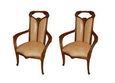 A pair of walnut arm chairs by Louis Majorelle.