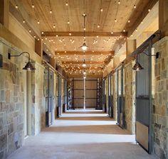 The stonework and ceiling lights add such a clean and new look. Such a beautiful barn. º Las luces de mampostería y techo agregan una mirada tan limpia y nueva, un hermoso establo.