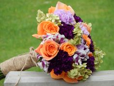 Purple Carnations of three kinds, orange Roses, Hydrangea and twine.  Made by Wedding Flowers By Cyndi, LLC