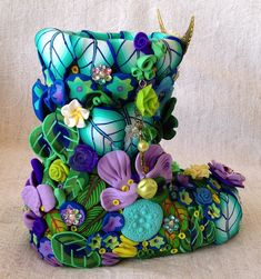 Blue, green, purple, and turquoise colored polymer clay flowers, leaves and pretties cover this boot. By yehudit yitzhaki.