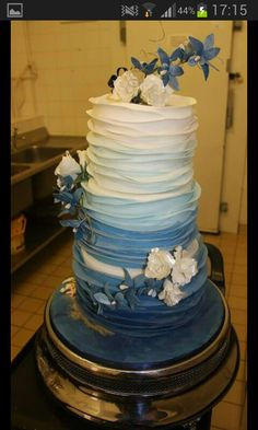 """Wedding cake with sugarpaste on the sjdes to resemble waves. The flowers are roses amd Singapore orchids. Around the side of the board is a small beach with shells, seahorses and """"sand"""". Ombre - from royal blue to white."""