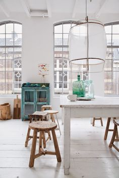 Vintage style dining area in white, wood, and turquois with wooden stools instead of chairs via Vosgeparis