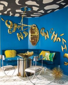 In Deborah Wecselman's dining room, the custom-designed banquette is covered in a Holly Hunt velvet, the light fixture is by Billy Cotton, the vintage gold letters are from the designer's collection, and the walls are painted in Ralph Lauren Paint's Baltic Blue.