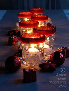 Christmas table in silver and red: floating candles in jam jars with a velvet rim. The inside of the rim is covered in red glitter to cover the thread. Cheap idea - elegant look!