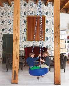 """The family strung up a tire swing smack dab in the middle of the living area. """"It's hours of fun for Luca and his friends,"""" says Rebecca, who replaced the swing's original industrial metal chain with a blue-and-white rope from Home Depot to give it a softer feel and help it fit in with the room's decor. Playmor tire swing, in Blue, sassoconstruction.com."""