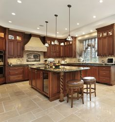 Luxurious custom wood kitchen design with a large island.  Huge work aisles and plenty of counterspace in this U-shaped kitchen.