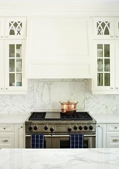 Anne Hepfer - beautiful white kitchen, marble backsplash, glass-front cabinets - note narrow cabinet door flanking range, they are pull-out shelves