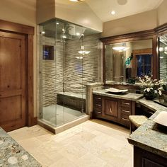 Likes: the shower ROOM with seat, unusual shape, his/her sinks with her vanity, wood door, wood framing of mirrors, lighting.