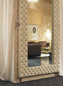 Large Upholstered Mirror in soft capitonne cream Leather. note black couch in the background.