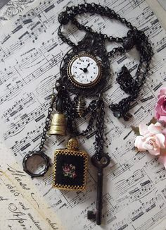 June. Challenge, Rusty Black pieces from B'Sues & vintage petit point perfume bottle, thimble, clock face and rusty key. Freshwater cultured black pearl in vintage brass cage swirl and Czech faceted glass at end of adjustable chain
