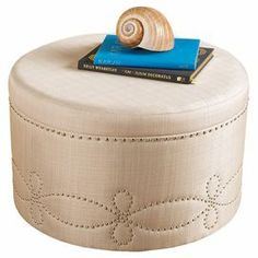 "Upholstered ottoman with nailhead detail.   Product: OttomanConstruction Material: Fabric, wood and brass Color: Cream Features: Perfect for additional seatingDimensions: 18"" H x 30"" Diameter"