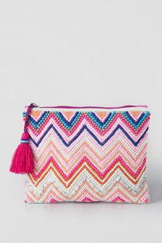 Summer is here as marked by the Daphne Beaded Clutch! The clutch features a vibrant summery color theme with pink, ivory, peach & blue beads placed in a chevron pattern with the back a pretty pink canvas. It is finished with a contrasting purple zipper & large pink tassel decoration.