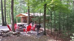 Red Roof Log Cabin showing fire pit and 6 adirondack chairs