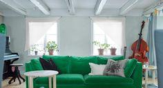 Wohnzimmer mit einem 3er-Sofa in Grün und selbst gebastelten Gardinen
