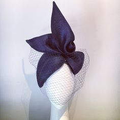 Beautiful straw piece with stylised bow detail and wrapped in matching veiling