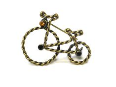 """Use code SOCIAL15 for 15% off all purchases over $15, plus FREE shipping on most jewelry! Bicycle brooch, wire wrapped bike, rhinestone wheel hubs and headlight, gold tone metal, twisted wire  It measures 1 1/2"""" (3.8 cm) by 1"""" (2.5 cm) and is in very good vintag... #etsygifts #vintage #vjse2 #jewelry #gift"""