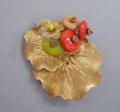 HASKELL Hess orange, chartreuse and tan bead dress clip with gold tone lily pads, 2-3/4. A Frank Hess design for Miriam Haskell, it is unsigned as was typical for this era, circa 1940.