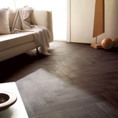 A rich, matte wood look porcelain tile set in a herringbone pattern - the perfect way to take a living room from casual to modern elegance.