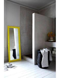 baño con encimera y ducha de obra acabado microcemento, suelo parquet, espejo con marco amarillo como contraste