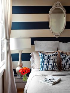Bold horizontal navy-and-white stripes wake up this bedroom that's tight on square footage but big on style. Design by Brian Patrick Flynn