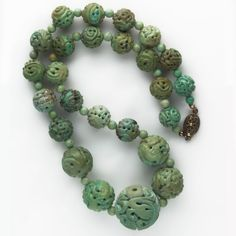 A 24 inch necklace of old Chinese carved green turquoise beads. These are genuine turquoise beads of natural color. Each bead is unique and colors are not uniform. You can see  matrix veins, includsions and  bands of color inmost of the beads. These beads range from green to a bluer turquoise, and the matrix is very distinct in some of them. Strung with alternating  5mm turquoise beads and a sterling silver push-in clasp. The beads are huge, ranging from 28mm in the center to 14mm at the…