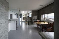 intérieur minimaliste gris - cuisine avec des armoires blanches, murs aspect béton exposé, table et chaises en bois