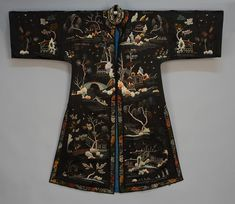 Chinese embroidered silk robe, mid 20th c.Black decorated with landscape having bridges, fisherman and figures in houses, with banded collar and side slits, small satin frogs (one missing), blue silk lining