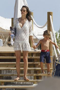 Sweet: She held hands with her little boy as they made their way down some steps...