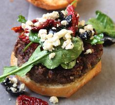 Parsley, dill, cumin, and garlic give these burgers a lively flavor reminiscent of a lamb gyro. The burger is enhanced by a tangy topping of feta, arugula, olives, and sun-dried tomatoes. The recipe is based on one from Michael Psilakis, the chef at Anthos, a New York City restaurant.
