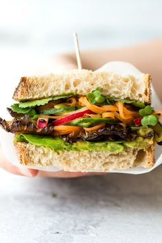 Asian mushroom sandwich has a satisfying range of flavours and textures that complement one another - smoky grilled mushroom, creamy avo, sharp pickles and fragrant herbs hide between two slices of sourdough bread. Vegan and can be gluten-free too.