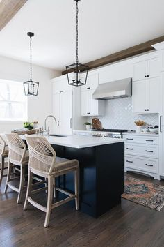 Transitional kitchen with a black center island and white perimeter cabinets both display white quartz countertops with black Darlana Mini Lanterns overhead.