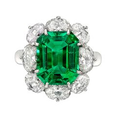 Octagonal emerald-cut emerald ring with an oval-shaped near-colorless diamond surround, the emerald weighing 6.10 carats and eight diamonds weighing approximately 4.00 total carats, mounted in platinum, with a hinged shank. Comes with GIA certificate.