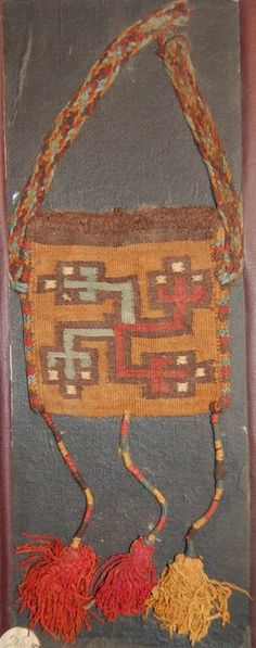 Mazca-Huari . Complete bag; camelid; dovetailed tapestry, cross knit loop stitching at edges, braided strap and three wrapped tassels at the bottom; main ...