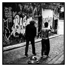 A Street Scene (2016).  I would say this is a typical street scene, but it looks anything but typical. I captured these two walking down Hosier Lane in Melbourne. The story it tells is your's to make up.  Melbourne, Australia. Image © Gary Light (8942, Oct 2016). License: (CC BY-NC-ND 4.0).  #photography #street #melbourne #victoria #australia #streetphotography #city