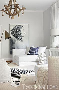 Oversize brass floor lamp and wood chandelier provide sculptural elements - faux zebra hide on top of sisal rug - oversize artwork - Designer Lisa Sherry