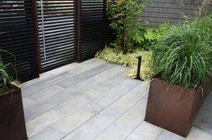 Steel planters were already being used in the backyard, and Estes incorporated them into the front yard design. The raised planters help sha. Palm Trees Landscaping, Side Yard Landscaping, Modern Landscaping, Landscaping Design, Landscape Materials, Garden Landscape Design, Front Yard Design, Patio Design, Good Neighbor Fence