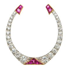 Art Deco Diamond Ruby gold platinum Horse Shoe Brooch. Vintage Art Deco design makes a classic horse shoe motif simply dramatic. Brilliant cut diamonds are set in platinum and rich yellow gold is added to hold beautiful calibrated rubies.