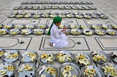 A Pakistani boy prays next to plates of fruits donated to worshippers to break their fast, on the first day of the holy fasting month of Ramadan, in a mosque in Karachi on July 21