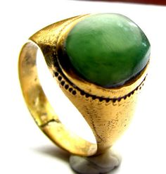 I have a serious crush on this ring. It is from the Georgian Era (late 18th Century) and it has a sizable piece of a smooth Green Jade cabochon as the centerpiece and it is in a Gold gilt setting. It