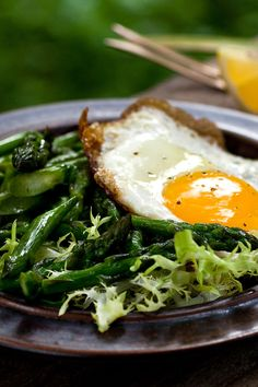 NYT Cooking: Here is a fine variation on the old combination of egg and asparagus. It is a twist on the bistro staple, frisée aux lardons, with pan-fried asparagus standing in for the bacon lardons. It's mixed with the frisée and a pungent garlic vinaigrette laced with a little anchovy. Then, in place of the usual poached egg nestled in curling frisée leaves, fry an egg until t...