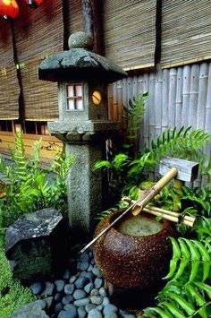 A small Japanese garden are with a lamp and vase fountain.