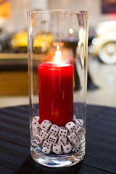 Fill with dice and black stones. Glass vase should be shorter and sit on top a black candle stick