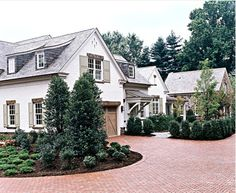 country/tudor -- beautiful brickwork, landscaping, and, especially, barn-style garage doors. love. white, distressed wood, gray shingling