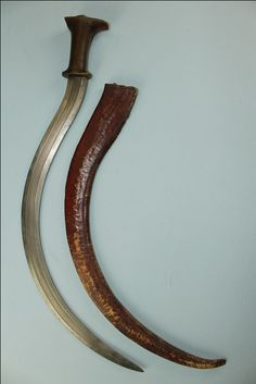 native Ethiopian Shotel sword - 69cms across the deeply curved blade. The hilt is cut from a single piece of Rhino horn. The blade is set with a full tang that is peened over a large silver domed pomme. The scabbard is very well preserved and slightly shrunken with age. It is constructed from leather and was dyed an earthy red colour.