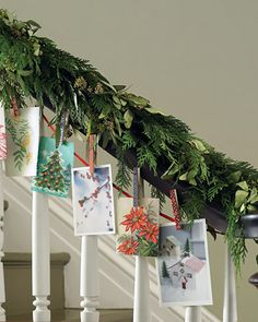 Cards hanging from banister It's hard to think of something fun to do with a banister, but this card garland is a great idea. Just add some bright ribbon (you can even use scraps).
