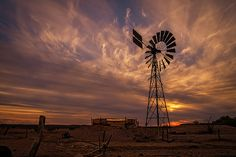An Australian windmill silhouette and cloudy sky at sunset.