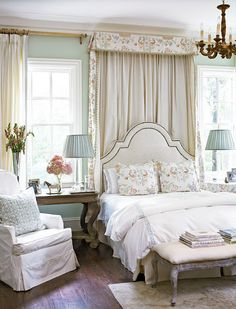 bed between two windows, drapes pulling from one side only here , nice wood floor