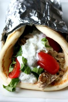 Instant Pot Chicken Gyros--tender, juicy seasoned chicken and onions piled onto soft pita bread and topped with a creamy cucumber yogurt sauce.